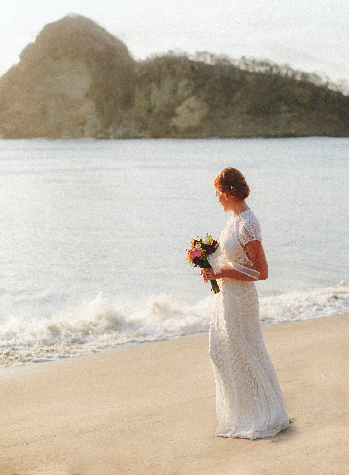Photography of a redhead Bride in stunning wedding dress walking at the beach after her wedding in Nicaragua